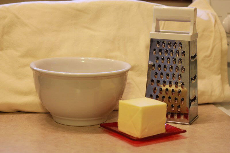 shredding chilled butter with a cheese grater